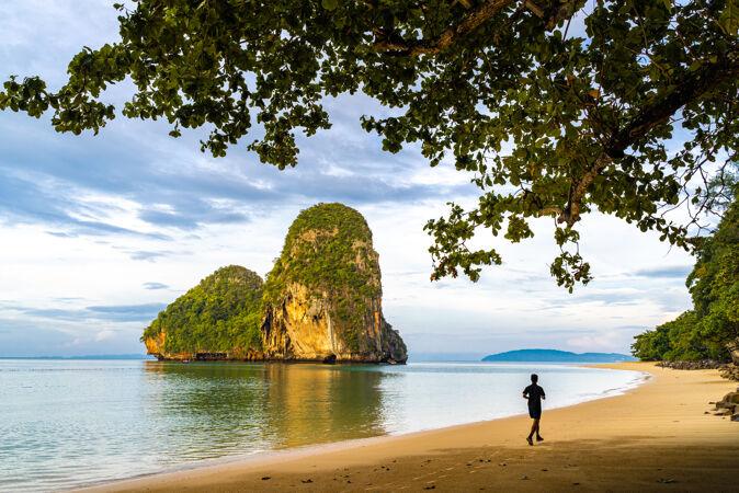 一个男人早上在泰国克拉比雷莱的普拉南洞海滩跑步