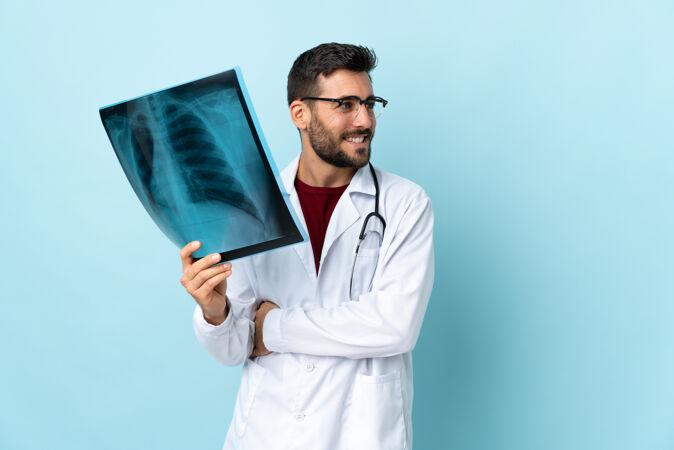 专业的创伤科医生拿着隔离在蓝色背景上的X光片往侧面看