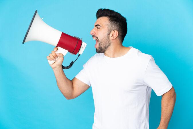 一名白人男子在孤立的蓝色背景下 通过扩音器大声喊叫 宣布在横向位置的东西