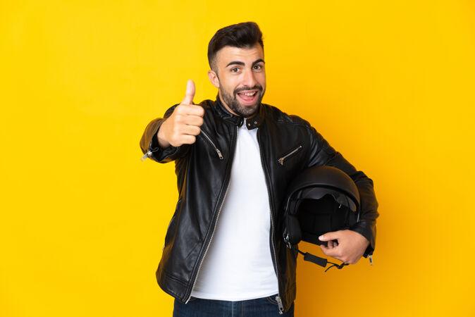 高加索男子戴着摩托车头盔在孤立的黄色背景下竖起大拇指 因为发生了好事