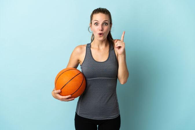 年轻女子在蓝色背景上孤立地打篮球 想在举手之劳的同时实现解决方案