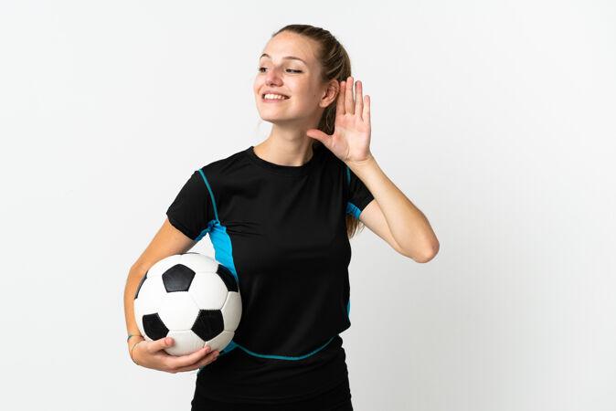 一个年轻的足球运动员 一个被隔离在白色背景下 用手捂着耳朵听东西的女人
