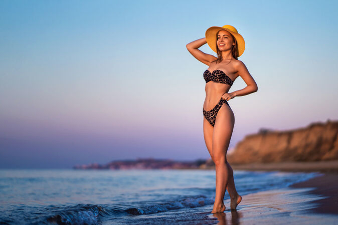 漂亮的黑发女人在海边的海滩上放松