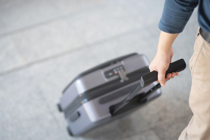 商人提着行李在公共交通大楼外匆忙行走营业时间现代机场旅客拉行李箱候机楼.行李出差