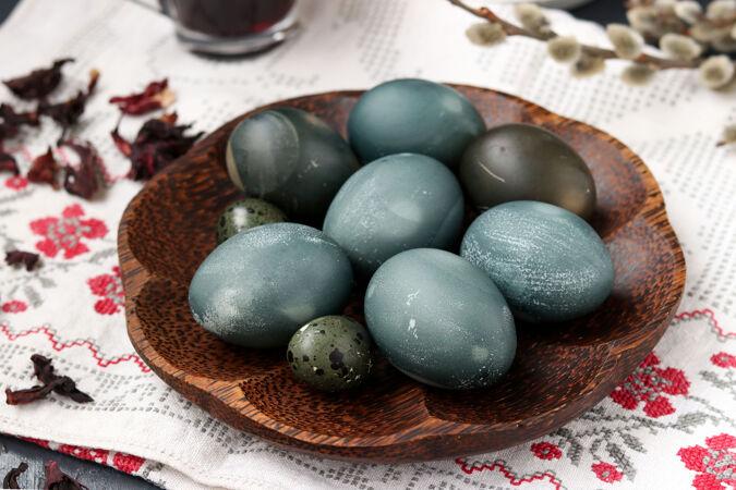 把复活节鸡和鹌鹑蛋放在盘子里 用苏丹玫瑰或芙蓉的花瓣涂上茶叶