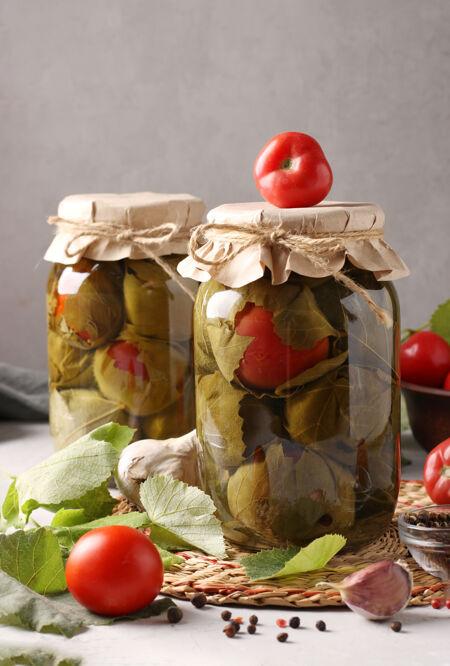 在灰色表面的两个玻璃罐中用葡萄叶腌制西红柿和大蒜