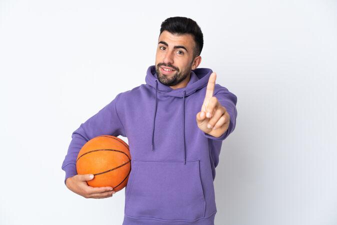 在隔离的白色墙壁上打篮球的人伸出一根手指