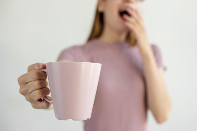 拿着咖啡杯模型的金发女人