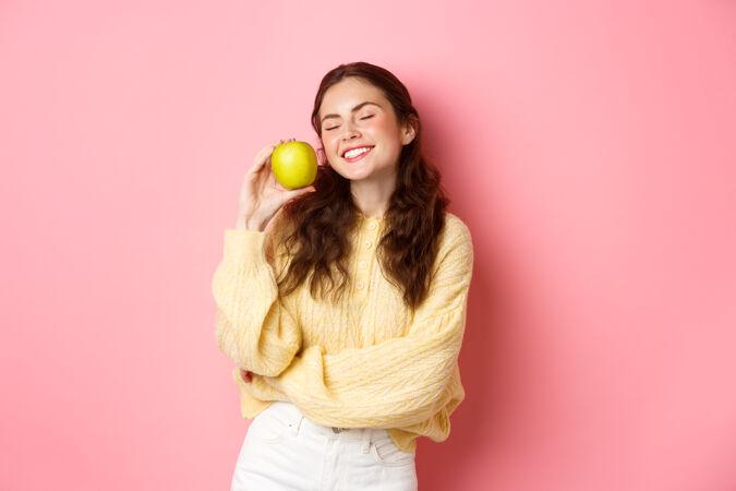 健康 口腔和人的概念快乐女孩展示她洁白完美的牙齿 微笑和绿色的苹果 吃健康的食物和水果 站在粉红色的墙上