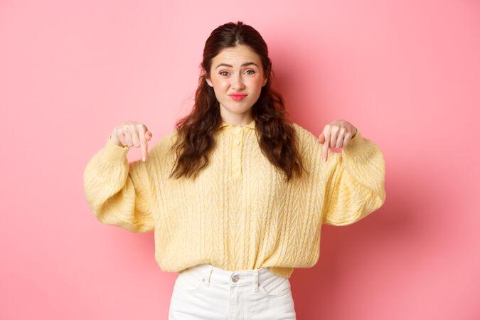 怀疑和不高兴的年轻女子因厌恶而做鬼脸 皱着眉头 用手指指着不好的宣传片 心烦意乱地站在粉红色的墙上