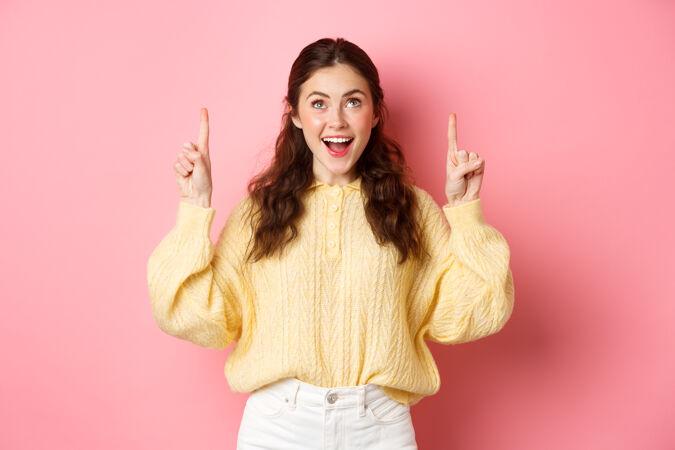 兴奋的黑发女孩指着手指 脸上带着兴奋的神情抬起头来 阅读宣传文字 查看广告 站在粉红色的墙上
