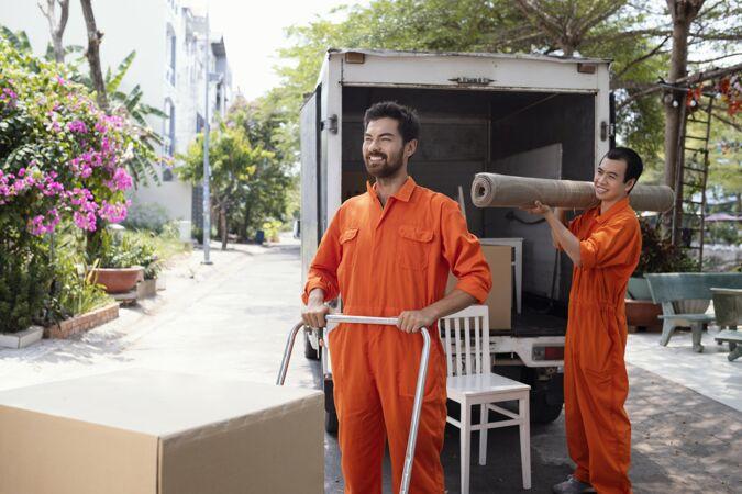 年轻的送货员从送货车里搬东西