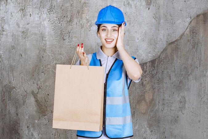 身穿蓝色制服 头戴安全帽的女工程师拿着购物袋 看上去很惊讶