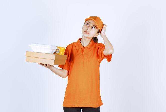 身着橙色制服的女快递员手里拿着一个纸板箱 一个塑料外卖箱和一个黄色的面杯 神情迷茫 若有所思