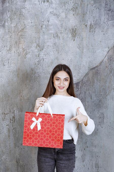 穿着白衬衫的女孩手里拿着一个红色的购物袋