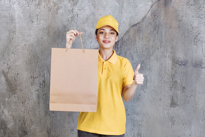 身着黄色制服的女服务人员手持购物袋 并显示积极的手势