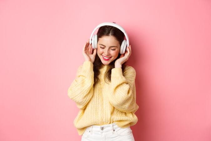 迷人的黑发女孩的肖像欣赏音乐 跳舞和微笑高兴 站在粉红色的墙壁复制空间