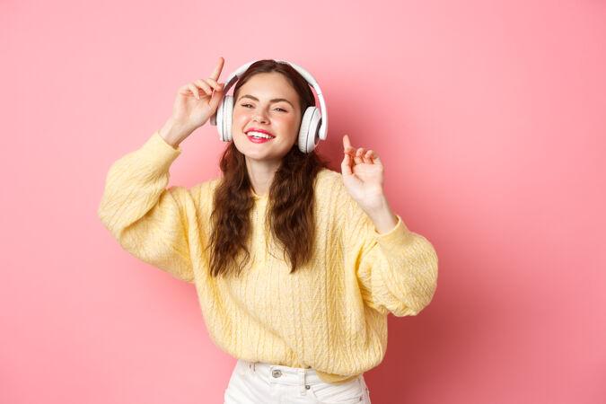 美丽时尚的女模特唱着最喜欢的歌 戴着无线耳机听音乐 微笑着跳舞 站在粉色的墙上